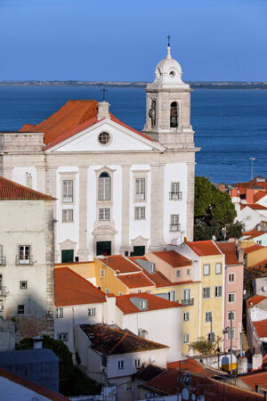 Baroque, 18th century Santo Estevao church in Lisbon, Portugal. Tagus river in the background. photo