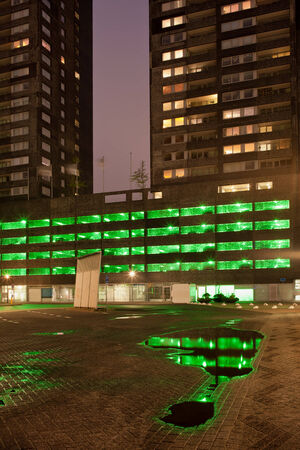 multi storey: Green lights of a multi storey car park with reflections on water after the rain at night, urban abstract in Rotterdam, Holland, Netherlands. Stock Photo
