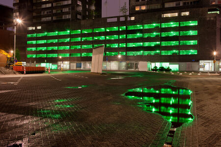 multi storey: Urban abstract, green lights of a multi storey car park with reflections on water after the rain at night in Rotterdam, Netherlands. Stock Photo