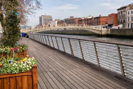 dublin ireland: Boardwalk along river Liffey and Hapenny Bridge in the city of Dublin, Ireland. Stock Photo