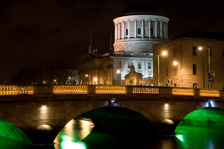 dublin ireland: Four Courts and bridge over river Liffey illuminated at night in the city of Dublin in Ireland.