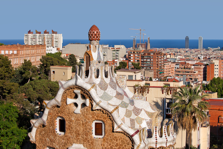 Casa del Guarda rooftop by Antoni Gaudi in Park Guell, and view over the city of Barcelona in Catalonia, Spain.
