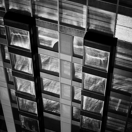 contrastive: Modern facade of an apartment building under construction, sunlight reflected on plastic foil secured windows.