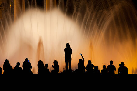 laser show: People silhouette against Magic Fountain illuminated at night in Barcelona, Catalonia, Spain.