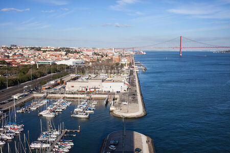 above 25: City of Lisbon in Portugal, Doca de Belem Marina, Tagus river quay and 25 de Abril Bridge at the far end.