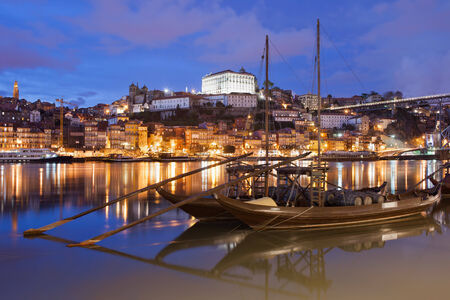 rabelo: City of Porto at night in Portugal. Rabelo traditional Portuguese cargo boats with wine barrels on Douro river and old city skyline.