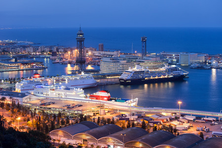 moll: City of Barcelona at night in Catalonia, Spain. Ships docked at cruise port terminal Moll Adossat, water of Mediterranean Sea.