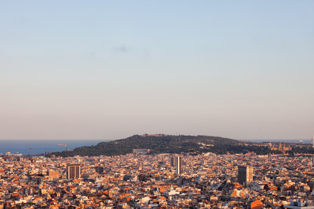 over the hill: View over city of Barcelona in Catalonia, Spain at sunset in the direction of Montjuic hill. Stock Photo