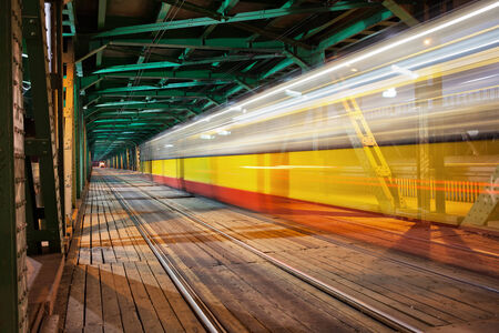 vanishing point: Tram light trail in the lower part of the steel truss Gdanski Bridge in Warsaw, Poland, vanishing point perspective.
