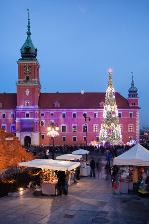 Royal Castle, Christmas Tree and souvenir stalls on Castle Square at dusk in the Old Town of Warsaw, Poland.