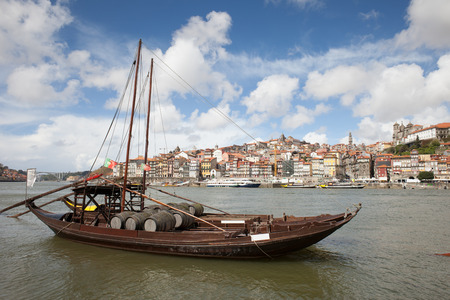 rabelo: City of Porto in Portugal. Rabelo traditional Portuguese cargo boat with Port wine barrels on Douro river.