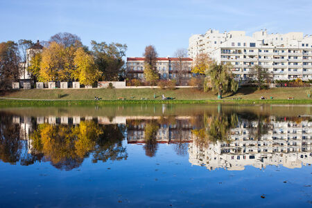 condominium complex: Skaryszewski Park in Warsaw, Poland. Apartment buildings and autumn trees by the lake with reflection on water. Editorial