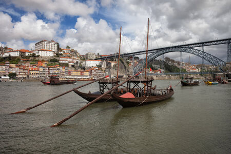 Rabelo traditional boats on Douro river, Dom Luis I Bridge, old city of Porto in Portugal.