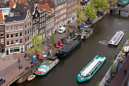 tour boats: City of Amsterdam in Holland, Netherlands, tour boats on a canal and traditional houses along Prinsengracht street, view from above.