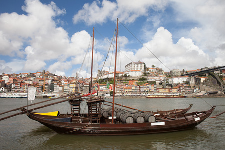 rabelo: City of Porto in Portugal. Rabelo traditional Portuguese cargo boat with Port wine barrels on Douro river and old city skyline. Stock Photo
