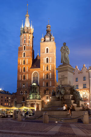 old town square: Krakow in Poland at night. St Marys Basilica (Mariacki Church) and Adam Mickiewicz monument on Main Square in the Old Town.