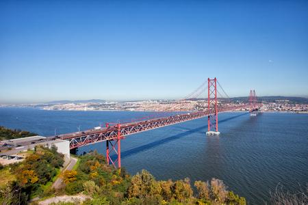 25th: 25 de Abril Bridge (Ponte 25 de Abril, 25th of April Bridge) over the Tagus river, connecting Almada and Lisbon in Portugal. Stock Photo