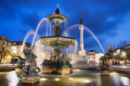 baixa: Fountain on Rossio Square at night in Lisbon, Portugal. Baroque style artwork with mythical creatures sculptures. Column of Dom Pedro IV in the background.