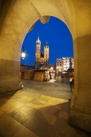 City of Krakow in Poland by night. Saint Mary Basilica and main square, view from the Cloth Hall (Sukiennice) arcade. photo