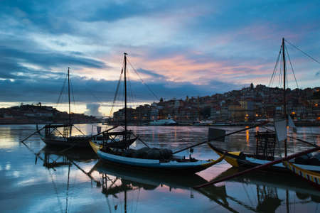 rabelo: Evening in the city of Porto, Portugal. Rabelo traditional Portuguese cargo boats with wine barrels on Douro river and old city skyline. Stock Photo