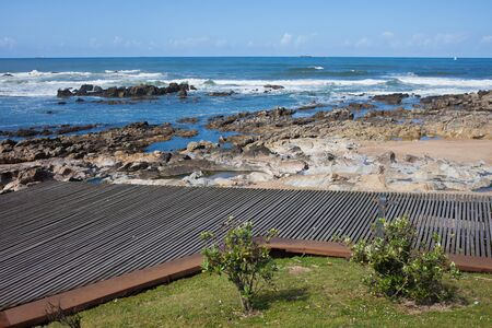 footway: Wooden promenade and rocky shore of the Atlantic Ocean in Porto, Portugal.