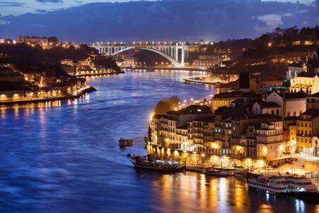 City of Porto and Gaia at night by the Douro river in Portugal, Arrabida Bridge at the far end. photo