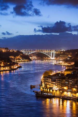 City of Porto and Gaia at night by the Douro river in Portugal, Arrabida Bridge at the far end.