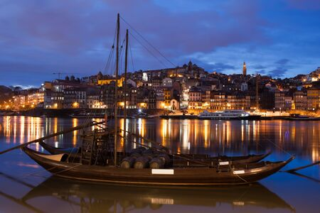 rabelo: City of Porto by night in Portugal. Rabelo traditional Portuguese cargo boats with wine barrels on Douro river and old town skyline.