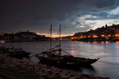 rabelo: Stormy evening sky above cities of Porto and Vila Nova de Gaia in Portugal, Rabelo boats on Douro river.