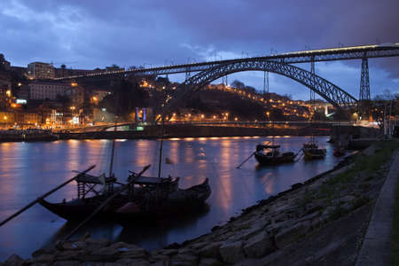 rabelo: Porto, Portugal, Dom Luiz I Bridge and Rabelo boats on Douro river in the evening.
