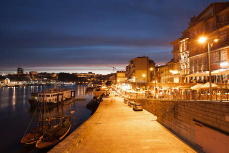 City of Porto by night in Portugal, promenade, boats and houses along Douro River, historic city centre.