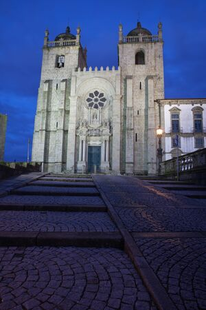 12th century: Porto Cathedral by night in Portugal city landmark founded in 12th century Romanesque and Baroque architecture. Stock Photo