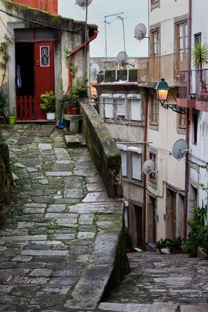 sloping: Medieval sloping alley in Ribeira Old Town of Porto in Portugal historic city centre. Stock Photo