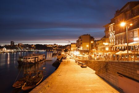 promenade: City of Porto by night in Portugal promenade boats and houses along Douro River historic city centre.