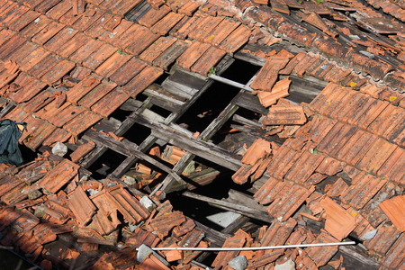 Hole in damaged clay tiled roof with wooden frame of a traditional building.