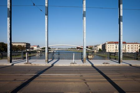 tramline: Street with tramline on Marshal Jozef Pilsudski Bridge over Vistula river in Krakow, Poland. Stock Photo