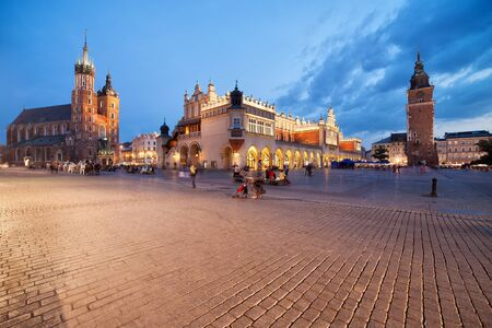 church architecture: Old Town of Krakow at dusk in Poland, Main Market Square, on the left St. Marys Church (Mariacki Church, Bazylika Mariacka) Cloth Hall (Sukiennice) in the middle, Town Hall Tower on the right.