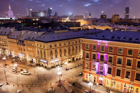 tenement: City of Warsaw in Poland by night, old apartment buildings and tenement houses on Krakowskie Przedmiescie street, downtown skyline.