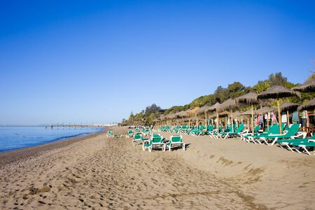 loungers: Beach witch sun loungers in Marbella, Spain, Costa del Sol, Andalucia region. Stock Photo
