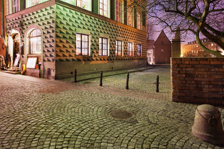 tenement: Cobbled street and old tenement house in Old Town of Warsaw in Poland at night. Editorial