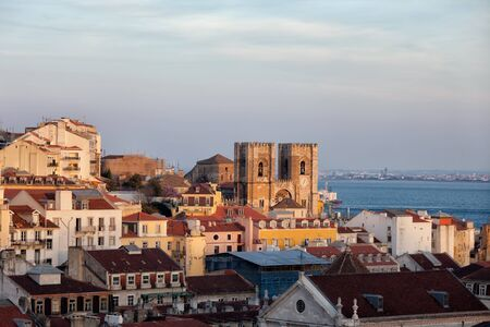 town houses: City of Lisbon at sunset in Portugal, old town houses skyline and Cathedral. Stock Photo