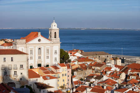 the tagus: City of Lisbon in Portugal, view over Alfama District with Santo Estevao church and Tagus river in the background.
