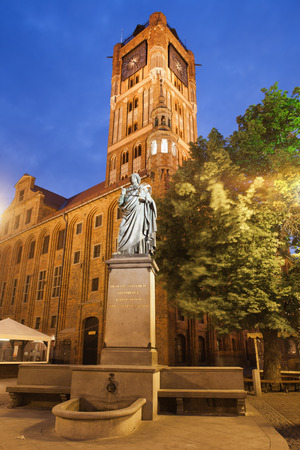 copernicus: Torun in Poland by night, Nicolaus Copernicus monument erected in 1853 and Old City Town Hall (Polish: Ratusz Staromiejski). Stock Photo