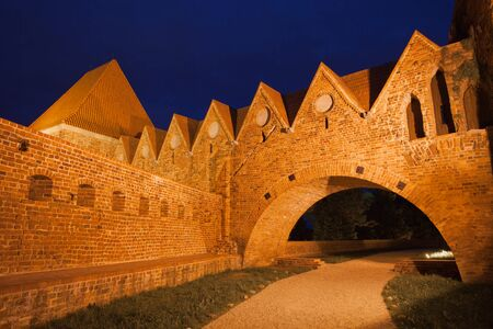 13th century: Teutonic Knights Castle at night in Torun, Poland, historic city landmark dating back to 13th century. Editorial