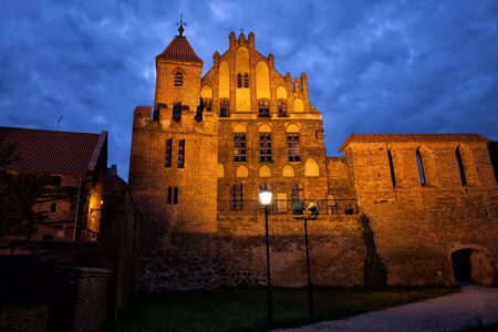 summer residence: Citizen Court by night, sentry tower and city wall in Torun, Poland, former summer residence of the Brotherhood of St. George, medieval Gothic architecture from 13-15th century.