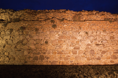 fortification: Teutonic Knights castle wall background illuminated at night in Torun, Poland, stone and brick medieval fortification.