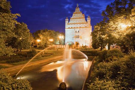 Park with fountain by night in Torun, Poland and Collegium Maximum of Nicolaus Copernicus University. Stock Photo