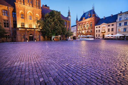 paved: Evening at Old Town Square in Torun, Poland, Town Hall (left), Artus Court (middle) and tenement houses. Stock Photo