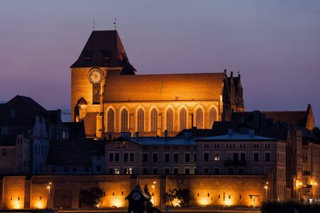 walled: Medieval walled city of Torun at night with illuminated Cathedral Basilica of St. John the Baptist and St. John the Evangelist.