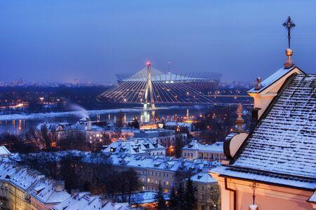 Varsovia noche de invierno paisaje urbano, ciudad capital de Polonia, vista hacia el río Vístula, Puente Swietokrzyski y Estadio Nacional, Santa Ana Iglesia a la derecha Foto de archivo